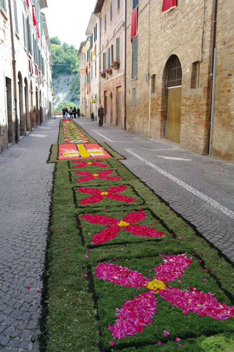 On Corpus Domini Sunday, Urbania decorates its streets with designs made only of flower petals, grasses, and the black border is coffee.